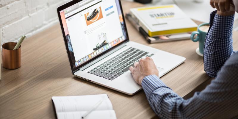 Man browsing through a website on his desk.