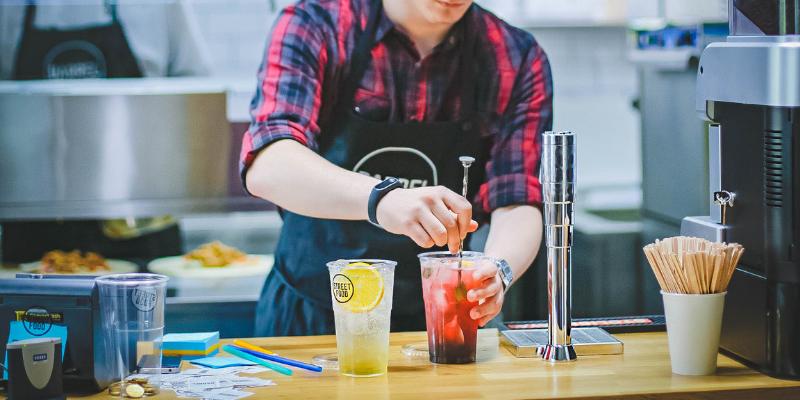 Restaurant employee preparing a beverage.