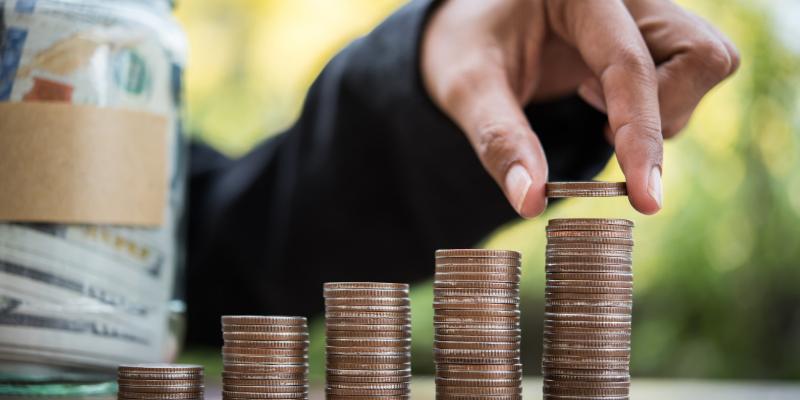 Man stacking coins next to a money jar.