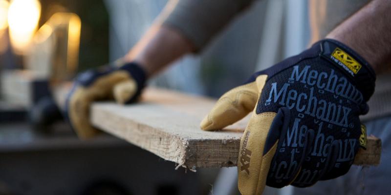 Person wearing the Mechanix Wear's Original Work Glove while cutting wood.