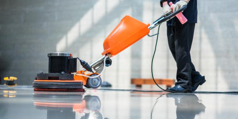Man using a floor scrubber in an office.