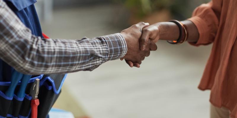 HVAC technician shaking hands with customer.
