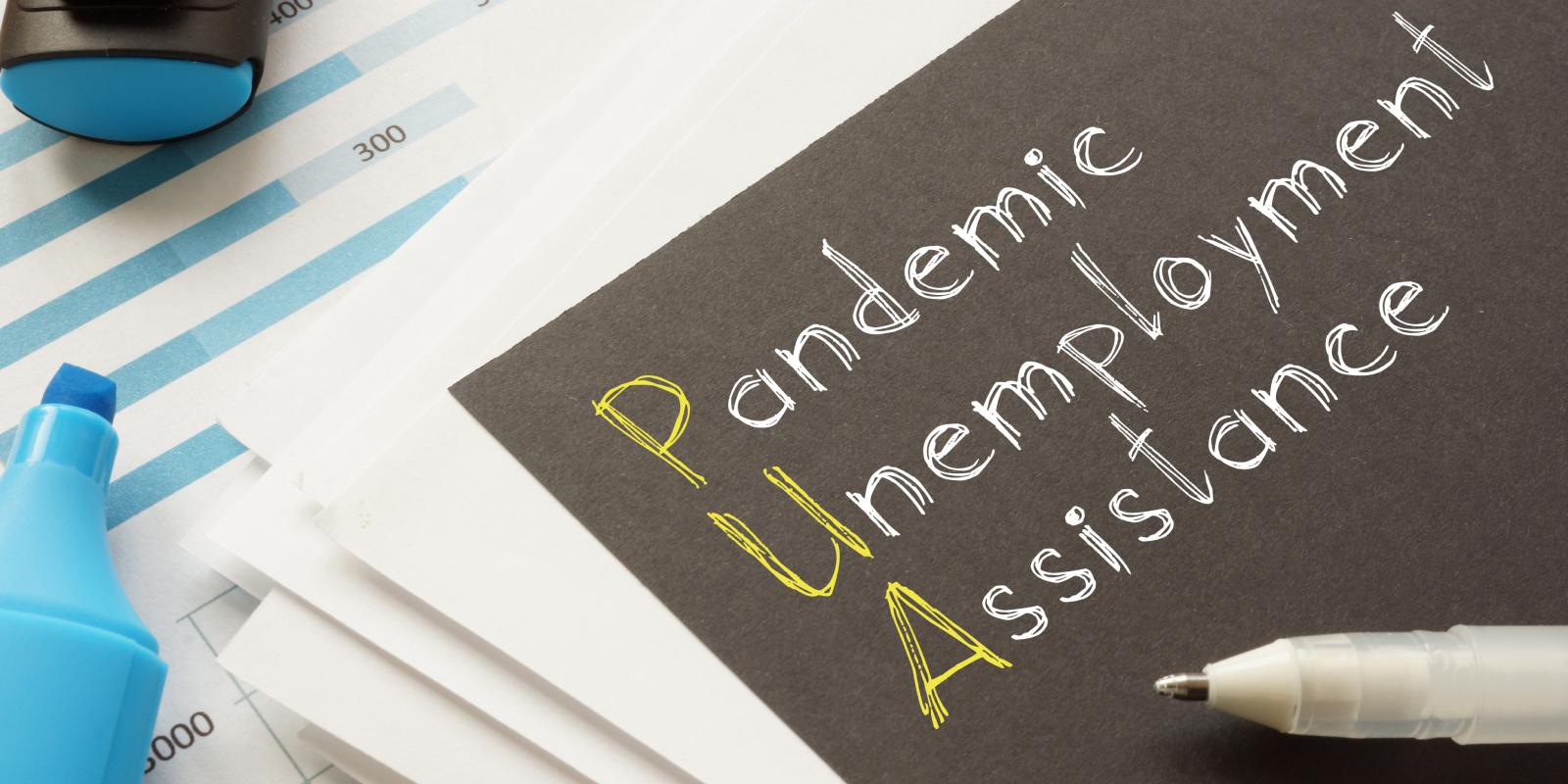 pandemic unemployment assistance written on a black piece of paper